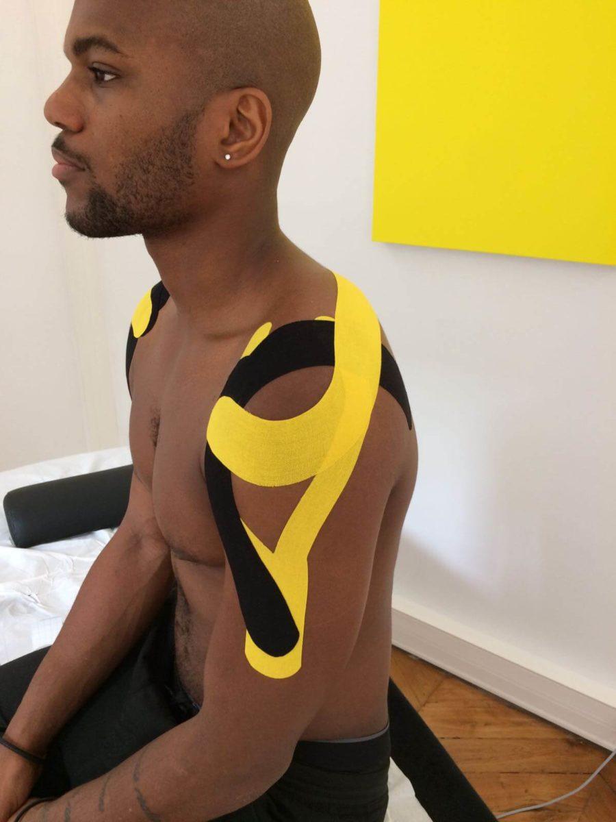 Homme assis vu sur le côté, portant des K-tapes sur les épaules